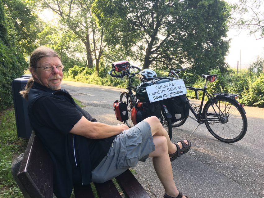 Mann auf Bank, zwei Räder