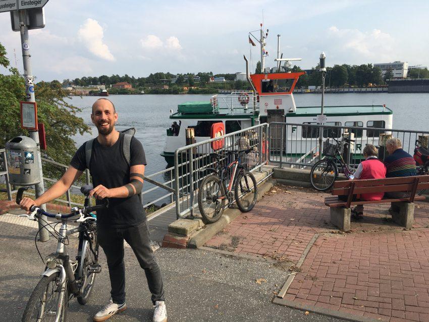 Mann mit Rad vor Holtenau-Fähre