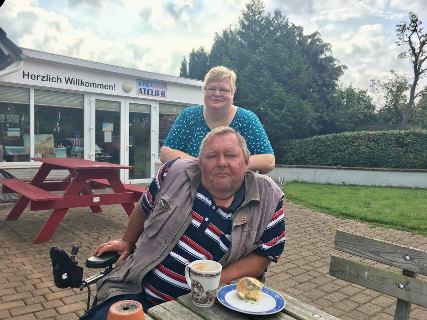 Mann im Rollstuhl, dahinter Frau