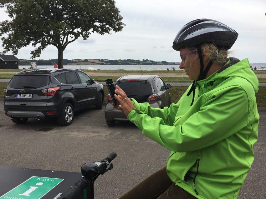 Frau auf Lastenrad bedient ein Handy