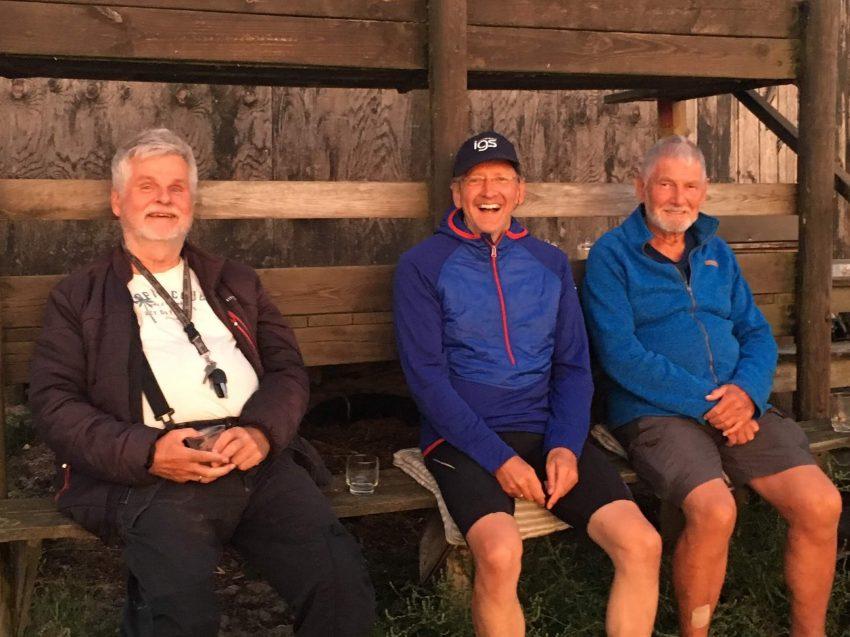 drei Männer mit Bier auf einer Bank