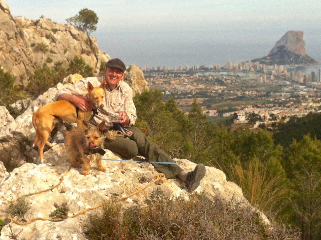 Mann mit zwei Hunden auf Bergspitze