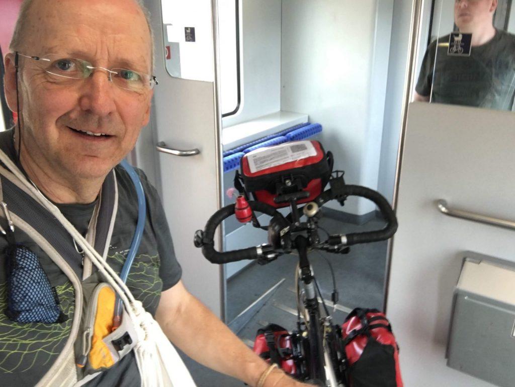 Mann mit Rad im Zug