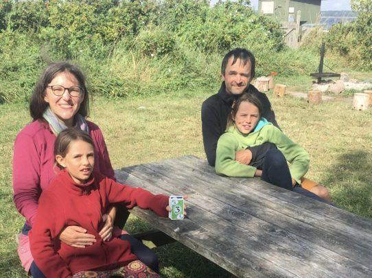 Familie mit zwei Kindern draußen am Tisch.