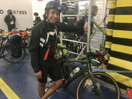 Mann in Fahrradkleidung und mit Rad unter Deck der Fähre