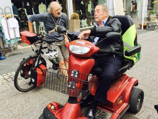 Rad- und Rollifahrer in intensivem Gespräch