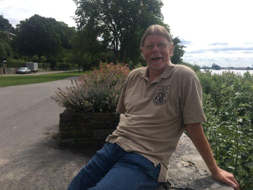 Mann auf Mauer vor Fluss