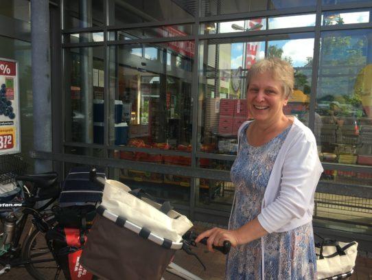 Frau mit Rad vor Supermarkteingang